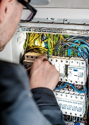 Anniston AL electrician working on circuit board